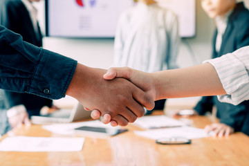 Entrepreneurs team collaborating deal shaking hands in a modern office.