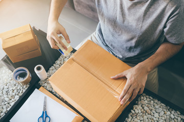 Asian entrepreneur teenagers are using the tape to seal the box by packing the product to send to customers.