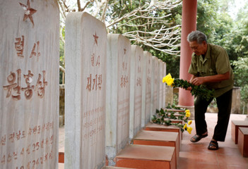 Vietnamese veteran Duong Van Dau places flowers on the headstones of North Korean pilots at the memorial site for North Korean pilots who fought and died during Vietnam War, in Bac Giang province