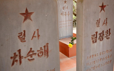 A flower is seen placed on the headstones of North Korean pilots at the memorial site for North Korean pilots who fought and died during Vietnam War, in Bac Giang province