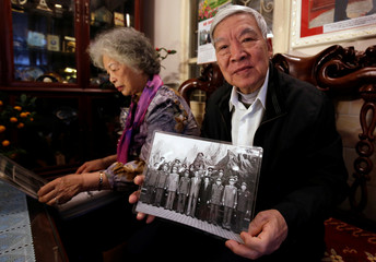 Former Deputy Defense Minister and former Vietnam War pilot Lieutenant General Tran Hanh shows a May 1994 archive photo of late North Korean Kim Il Sung with Vietnamese military delegation, at his home in Hanoi