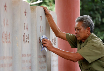 Vietnamese veteran Duong Van Dau cleans the headstones of North Korean pilots at the memorial site for North Korean pilots who fought and died during Vietnam War, in Bac Giang province