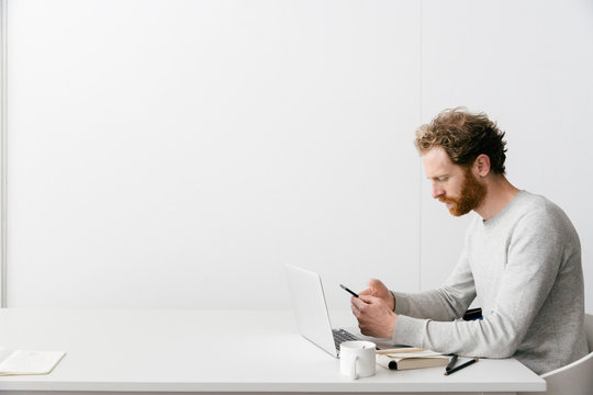 A thirty something man with a red beard and curly hair in a grey pull over is looking on his smart phone while working on his laptop in a clean white empty office setting.