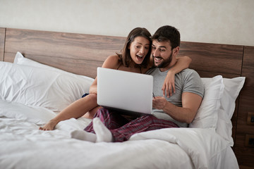 Happy couple lying on a bed with computer - Beautiful married couple watching sex video on laptop laughing together - People, sexual, technology concept.