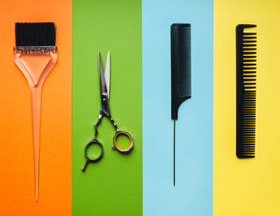 Tools hairdresser on the background of pastel paper in the form of multi-colored stripes....