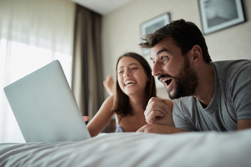 people, family, bedtime and fun concept -Couple with laptop in bed surfing on the net at laptop.