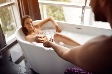 drinking champagne in the bathtub- couple relaxing together in the bathtub top view.