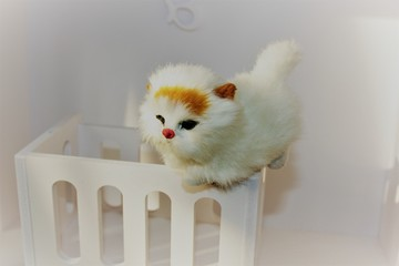 A small toy white kitten sits on a toy white cot in a children's house. Shabby Chic Style  in the interior of the children's room.