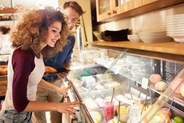 Girl choose fresh juice from showcase