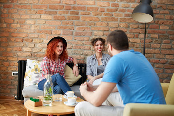 Man with two girls chat in cafe