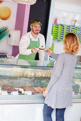 Salesman in candy shop gives cup cake to customer