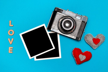 Vintage camera with two felt hearts and photo cards. Top view on blue background