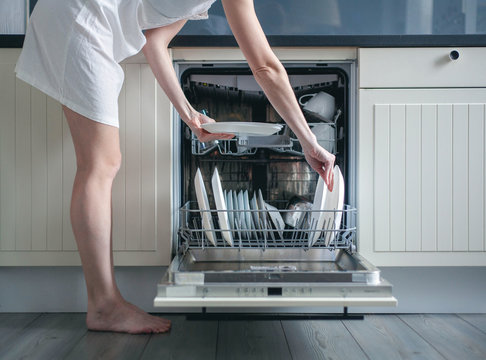 Woman loading dishes into dishwasher, High angle view of utensils in dishwasher at kitchen