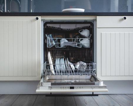Modern kitchen. High angle view of utensils in dishwasher at kitchen