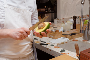 Chef is cutting a big avocado in halves