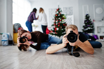 The team of two photographers lie on the floor and shooting on studio.
