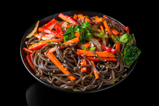 Soba Noodles (buckwheat) with vegetables: carrots, sweet peppers, broccoli on a black background. Sushi menu. Japanese food