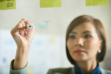 Business lady writing on glass wall