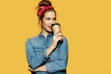 Portrait of charming young female sipping hot coffee on yellow background. Beautiful brunette lady in stylish clothes looking away. Copy space in right side. Lifestyle concept
