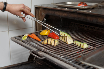Chef is cooking vegetables in charcoal grill