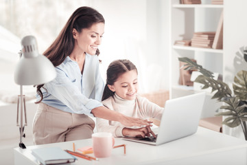 Caring smiling mother pointing at laptop showing daughter their family photos