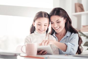 Helpful understanding mother teaching her funny energetic daughter reading