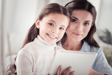 Kind loving mother feeling pleased watching at photo frame with her kid