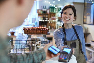 Male Customer Making Contactless Payment For Shopping Using Mobile Phone In Delicatessen