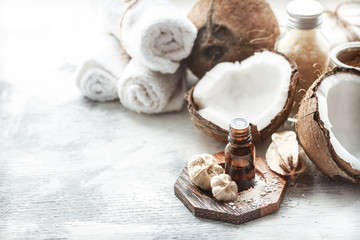 still life with coconut oil in a bottle and fresh coconut