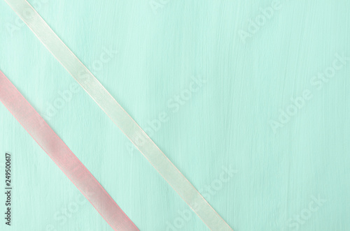 Two thin ribbons on blue-green colored surface, packaging