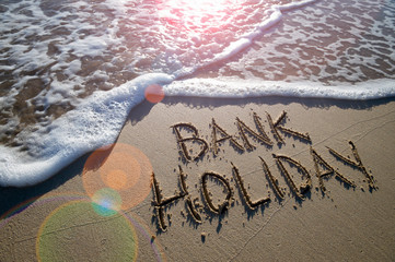 Bank Holiday message handwritten on the smooth sand of an empty beach with an oncoming wave