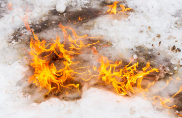Flame of fire on white snow in winter