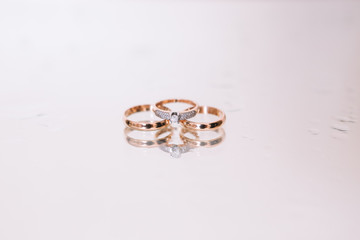 3 wedding gold rings on the white background glass with water drops . Wedding. Diamonds.