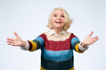 European senior woman raised up palms arms hands at you