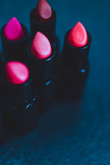 group of red pink and nude lipsticks with different colors and textures on dark table