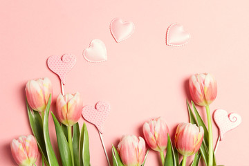 Floral frame background with tulip flowers and hearts on pink pastel background.