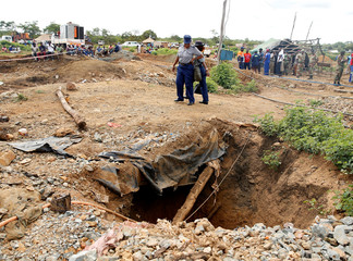 Police look on near a shaft as retrieval efforts proceed for trapped illegal gold miners in Kadoma