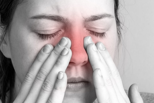 Young woman with sinus pressure pain on gray background. Pain in the nose.