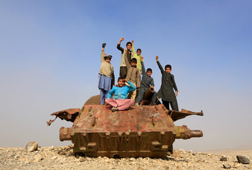Afghan children play on the remains of a Soviet-era tank on the outskirts of Jalalabad