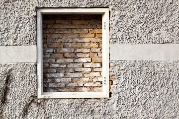 Brick wall behind a window frame