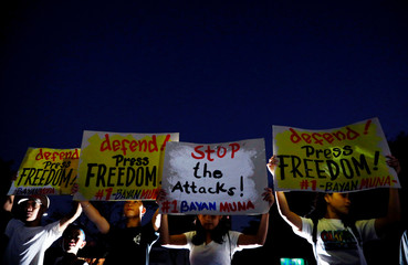 Protesters raise placards in a rally for press freedom in Quezon City
