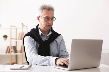 Senior businessman working on laptop at home office