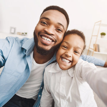 African-american father taking selfie with daughter at home