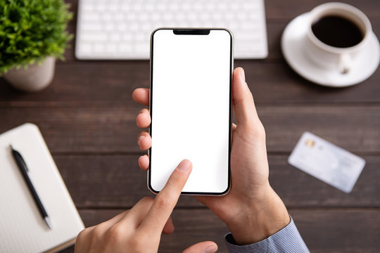 Man using blank smartphone on workplace desk