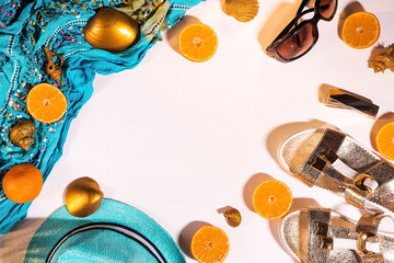 Cut in half orange tangerines lie on a blue tippet. Flat lay. A place for your inscription. Pure white background, handkerchief, hat, fruit, lipstick, Golden seashells, Slippers, summer concept