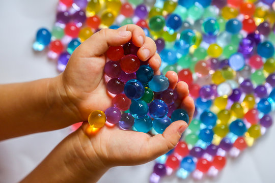 Colored balls of hydrogel in child's palms. Sensory experiences