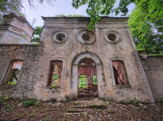 Old abandoned St. Nicholas Church ruins in Estonia. The lush foliage of trees and forest covering the beauty of this ancient ruined building.
