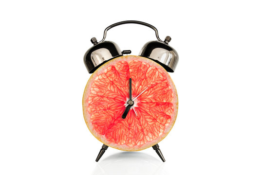 Grapefruiti slice on alarm clock, isolated on white background, fruit and vitamins diet at breakfast nutrition concept