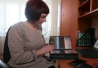 School teacher Olga Markelova, ex-wife of late Russian military contractor Dmitry Markelov, shows a photo album in Nizhnekamsk