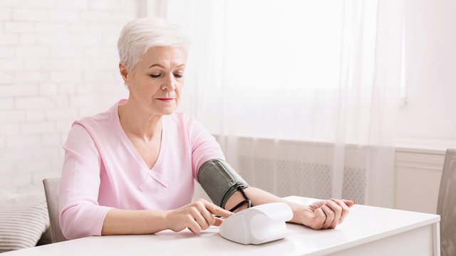 Senior woman measuring her blood pressure at home.